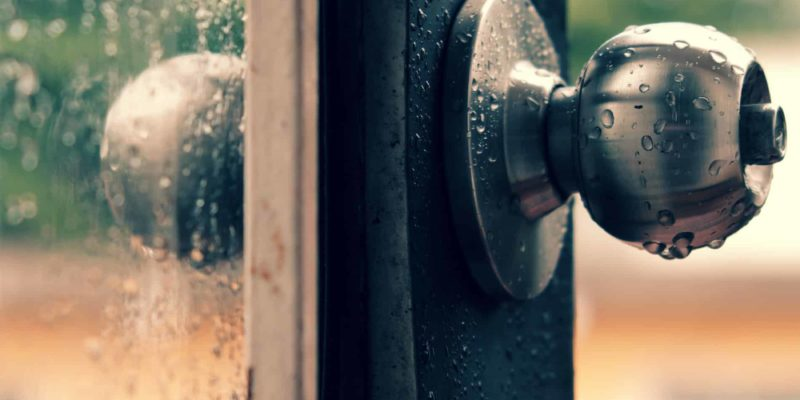 Rain drops on door handle and glass window in rainy day, drop of water falling make lonely feeling of cold day